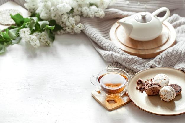 Gemütliche frühlingszusammensetzung mit einer tasse tee, einer teekanne, französischen makronen, lila farbe Kostenlose Fotos