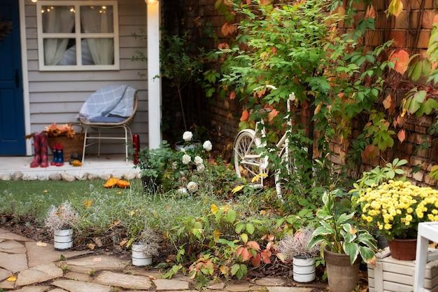 Gemütliche gartenecke des hauses mit zimmerpflanzen in töpfen. hausterrasse im dekor. Premium Fotos