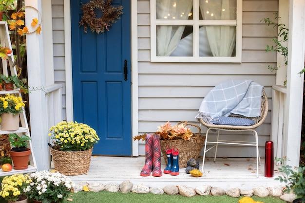Gemütliche herbstterrasse mit stuhl, plaid, gummistiefeln, körben mit chrysanthemen und kürbissen. Premium Fotos