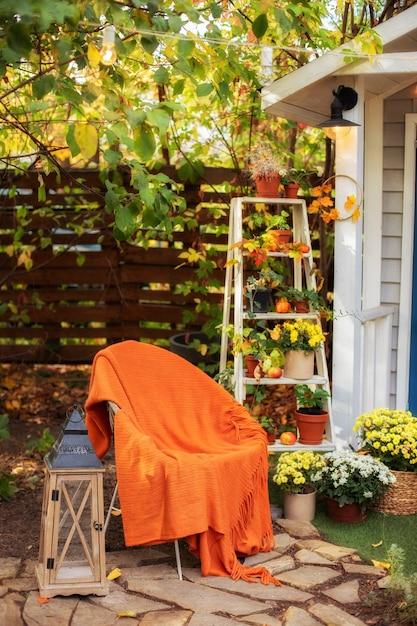 Gemütliche herbstterrasse mit stuhl, plaid, laterne, topfchrysanthemen. Premium Fotos