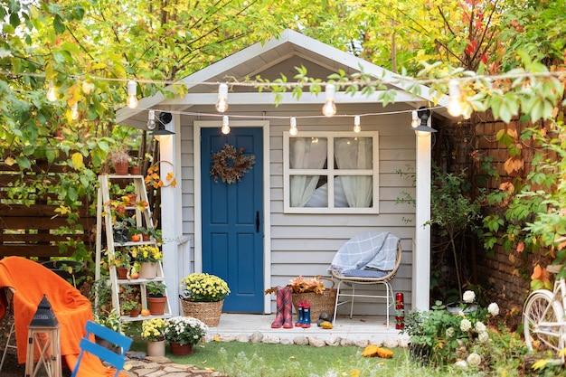 Gemütliche holzhausveranda mit stuhl, topfblumen. dekor des herbsthofes Premium Fotos