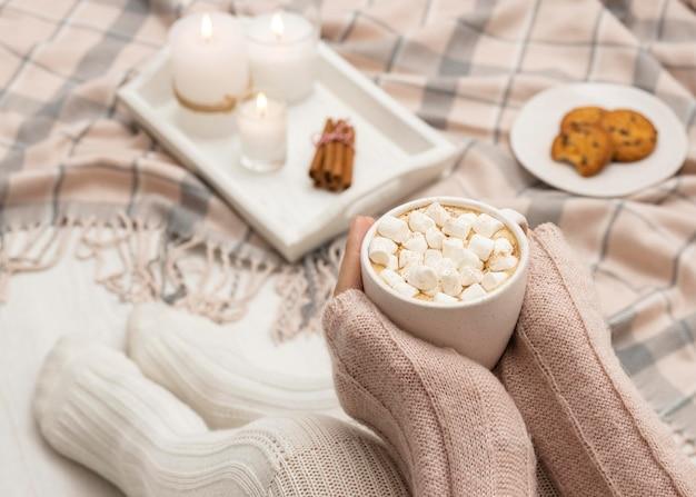 Gemütliche person, die becher mit heißem kakao und marshmallows hält Kostenlose Fotos