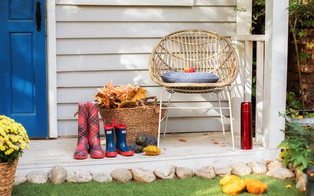 Gemütliche sommerterrasse mit stuhl, plaid, gummistiefeln. herbst holz veranda nach hause. gemütliche terrasse zum entspannen Premium Fotos