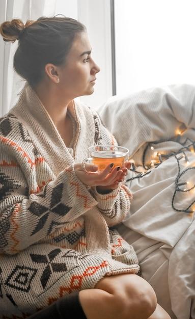 Gemütliche transparente tasse tee bei einem süßen mädchen in einem warmen strickpullover gegen das fenster Kostenlose Fotos