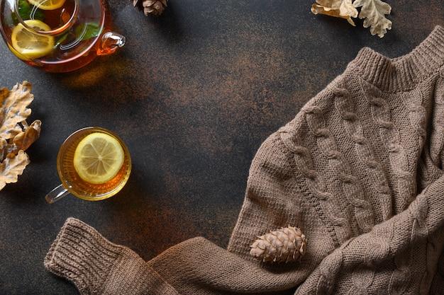 Gemütliche zusammensetzung des herbstes mit wärmendem tee, herbstblättern und pullover auf braunem hintergrund. ansicht von oben mit speicherplatz. Premium Fotos