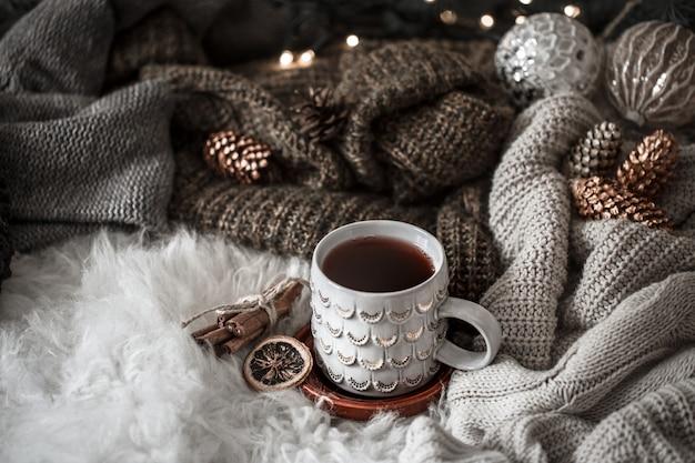 Gemütlicher weihnachtsmorgen mit einer tasse tee im bett. stillleben mit pullovern. dämpfende tasse heißen kaffees, tee. weihnachtskonzept. Kostenlose Fotos