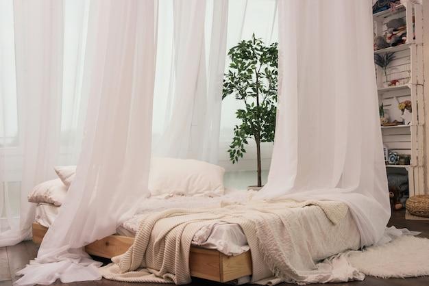 Gemütliches bett in der nähe des fensters mit schönen vorhängen im zimmer. Premium Fotos