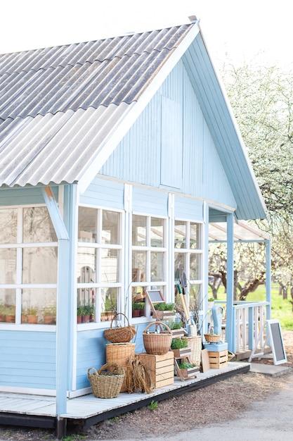 Gemütliches blaues haus mit einem schönen garten an einem sonnigen tag. rustikaler stil. herbstkonzept. haus auf dem land. englisches landhaus. schönes bauernhaus mit weidenkörben mit ernte. Premium Fotos