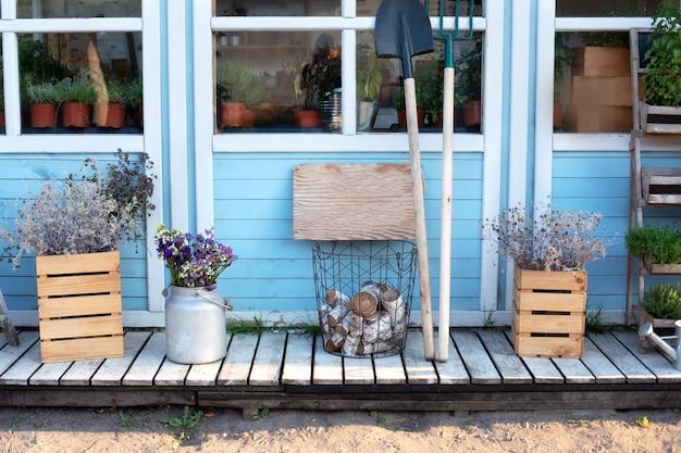 Gemütliches herbstdekor-veranda-haus. holzveranda des hauses mit pflanzen, protokollen. Premium Fotos