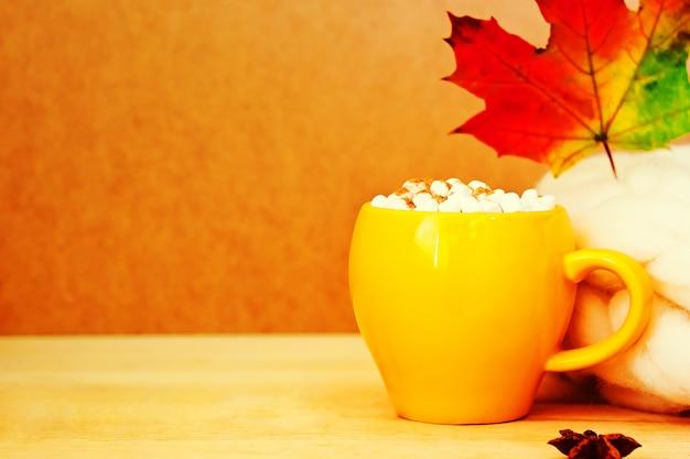 Gemütliches herbstkonzept mit gelber tasse kakao mit marshmallow und zimt Premium Fotos