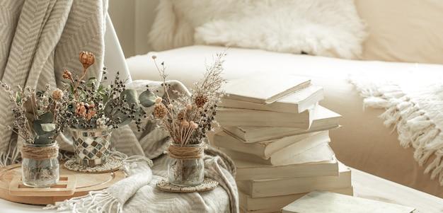 Gemütliches interieur des zimmers mit büchern und getrockneten blumen in einer vase. Kostenlose Fotos