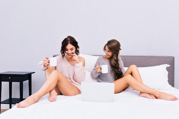 Gemütliches weiches bild von zwei jungen frauen in warmen wollpullovern, die auf bett in der modernen wohnung abkühlen. freudige mädchen trinken kaffee, kommunizieren, haben spaß zusammen. freunde, entspann dich, guten morgen. Kostenlose Fotos