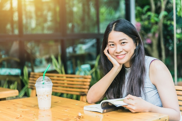 Genießen sie entspannende zeiten mit lesebuch, thailändisches jugendlich lächeln der asiatischen frauen mit buch im weinlesefarbton der kaffeestube Premium Fotos