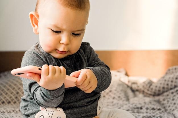 Genz-konzept der entwicklung des babygrifftelefonsitter-kleinkindes zuhause früher technischer Premium Fotos