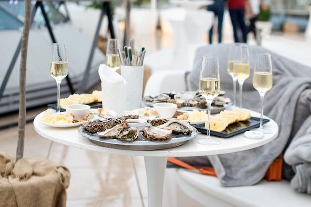 Geöffnete austern und zitrone mit weißwein auf dem tisch. Premium Fotos