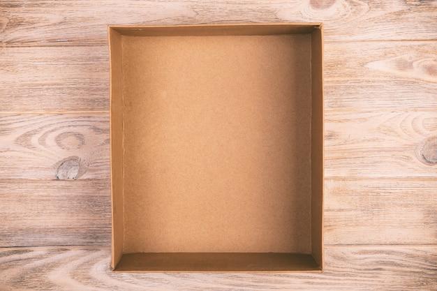 Geöffnete pappschachtel auf holz Premium Fotos