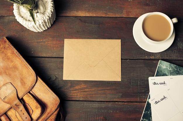 Geöffneter bastelpapierumschlag, herbstlaub und kaffee auf holztisch Kostenlose Fotos