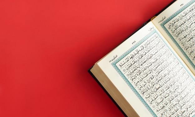 Geöffneter koran auf einem einfachen burgunderfarbenen raum Premium Fotos
