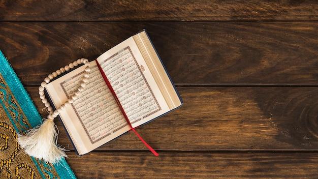 Geöffneter koran, der nahe matte liegt Kostenlose Fotos
