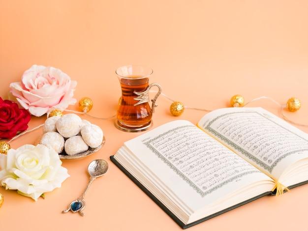 Geöffneter quran auf festlicher tabelle mit blumen Kostenlose Fotos
