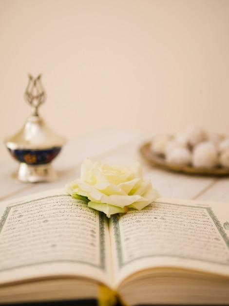 Geöffneter quran mit weißrose und defocused hintergrund Premium Fotos