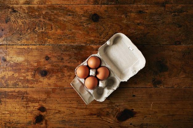 Geöffneter recycelbarer eierkarton für sechs eier mit vier großen braunen eiern auf einem rauen, rustikalen, braunen holztisch Kostenlose Fotos