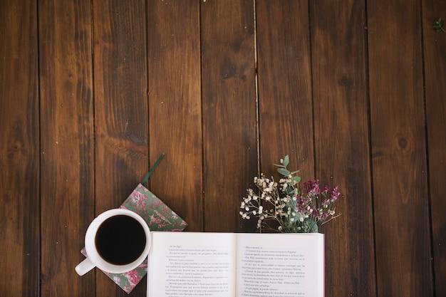 Geöffnetes buch und kaffee mit blumenstrauß Kostenlose Fotos