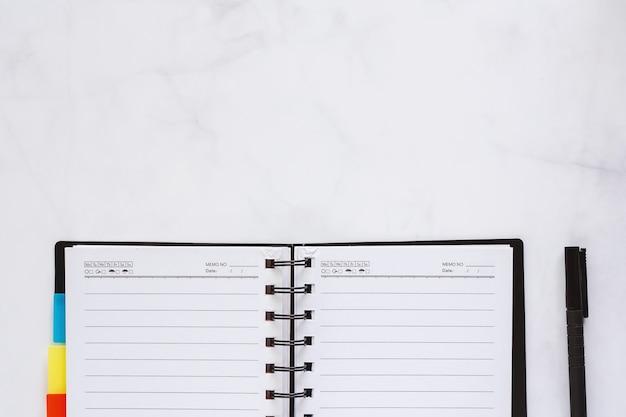 Geöffnetes gewundenes notizbuch mit schwarzem stift auf weißem marmorhintergrund für arbeitsplatzkonzept Premium Fotos