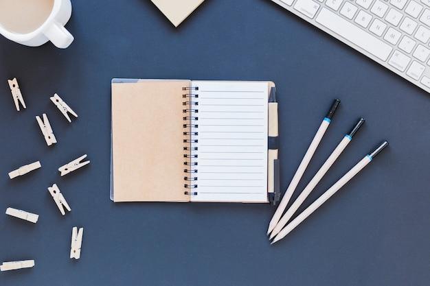 Geöffnetes leeres notizbuch nahe briefpapier und tastatur Kostenlose Fotos