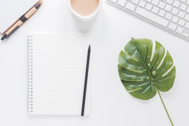 Geöffnetes notizbuch nahe kaffeetasse und tastatur auf tabelle mit grünem blatt Kostenlose Fotos