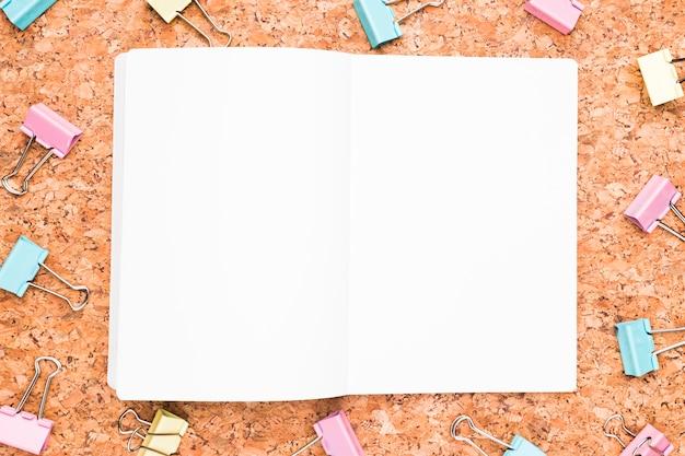 Geöffnetes notizbuch und mehrfarbige mappenclips Kostenlose Fotos