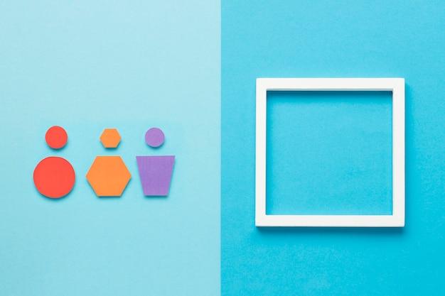 Geometrische formen in verschiedenen farben neben dem leeren rahmen Kostenlose Fotos