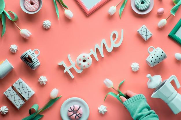 Geometrische frühlingswohnung lag in weiß und grün auf rosa hintergrund. ostern, muttertag, frühlingsgeburtstag oder jahrestag. kunststoff-heizbrett, ostereier, kaffeemaschine, tassen, tulpen, geschenke. Premium Fotos