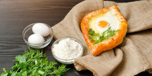 Georgische küche. khachapuri auf sackleinen, mehl, eiern. schwarzer tisch. Premium Fotos