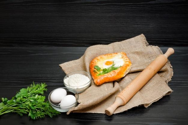 Georgische küche, khachapuri auf sackleinen, mehl, eiern und nudelholz. Premium Fotos