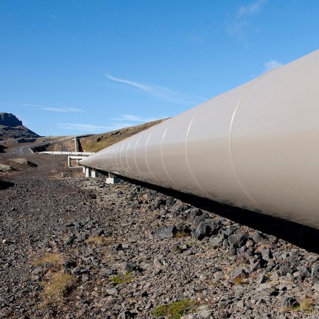 Geothermisches heizungsrohr durch isländische landwirtschaftliche landschaft Premium Fotos