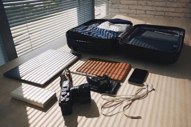 Gepackter koffer, der auf schreibtisch durch fenster mit vorhängen und elektronischen geräten in der nähe liegt Kostenlose Fotos