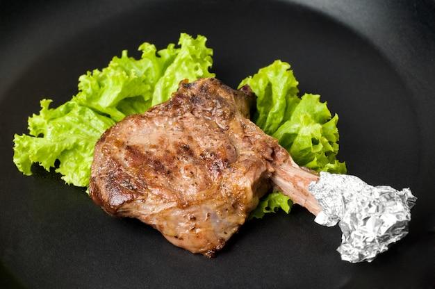 Gerade geröstetes saftiges ribeye-steak auf schwarzem teller oder pfanne mit anti-burn-beschichtung Premium Fotos