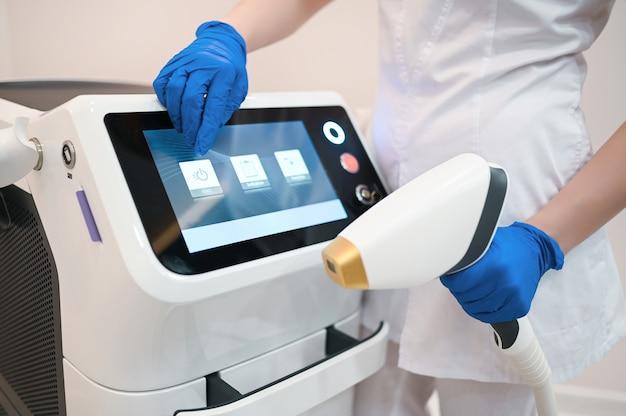Gerät zur laser-haarentfernung und die hände einer kosmetikerin kosmetikerin in medizinischen handschuhen. epilation und spa-konzept Premium Fotos
