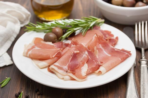 Geräuchertes fleisch mit oliven auf weißem teller Premium Fotos