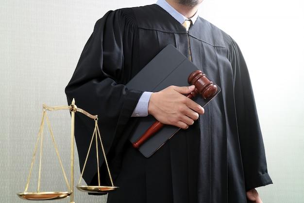Gerechtigkeit und recht konzept. männlicher richter in einem gerichtssaal mit der hammer- und balancenskala und der heiligen schrift. Premium Fotos