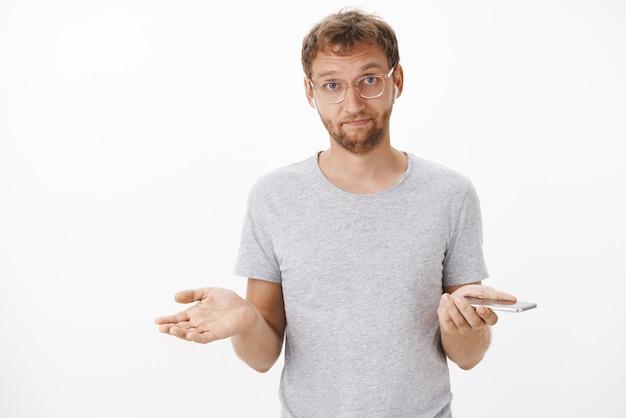 Gereizter gutaussehender kerl mit brislte in gläsern, die mit gespreizten händen in ahnungsloser geste zucken, die lied in drahtlosen kopfhörern hält, die smartphone halten Kostenlose Fotos