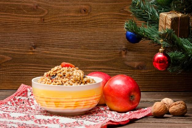 Gericht des traditionellen slawischen genusses am heiligabend. weihnachtsbaum, äpfel, walnüsse auf einer gemusterten tischdecke. braune holzwand. speicherplatz kopieren Premium Fotos