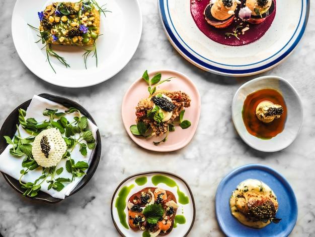Gerichte mit goldenem kaviar auf verschiedenen tellern Kostenlose Fotos