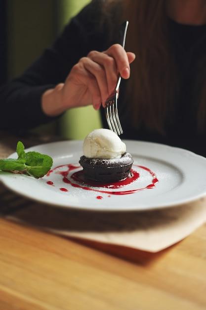 Geringe schärfentiefe foto von brownie-kuchen mit eis. hand des mädchens mit gabel. Premium Fotos