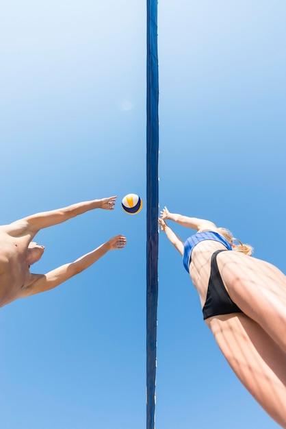Geringer winkel der volleyballspieler, die über das netz nach ball greifen Kostenlose Fotos