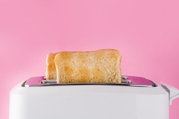Geröstetes toastbrot im weißen toaster an der rosa wand Premium Fotos