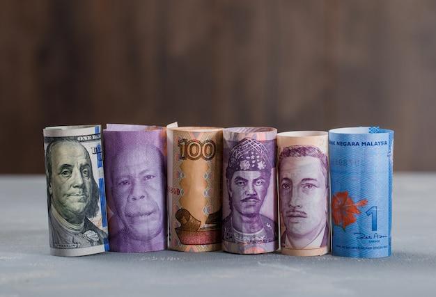 Gerollte banknoten auf gips und holztisch. Kostenlose Fotos
