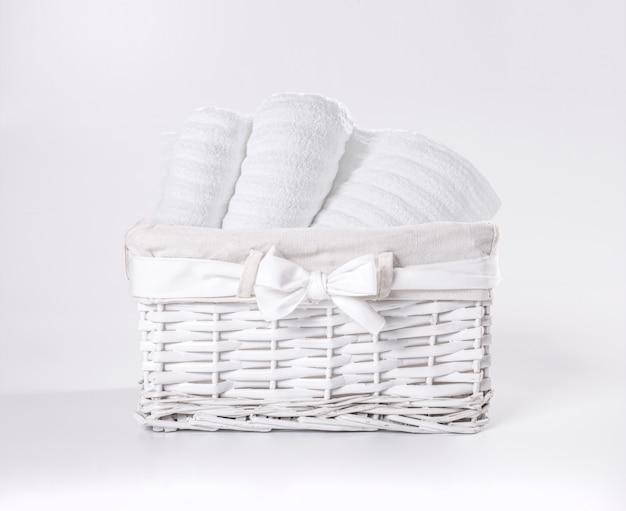 Gerollte weiße weiche frotteestoffe im korb gegen einen weißen hintergrund. gestreifte handtücher in einem weißen korb vor einem weißen hintergrund. Premium Fotos
