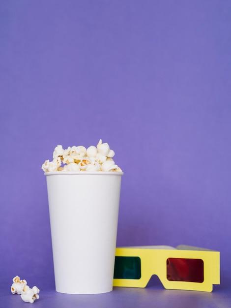 Gesalzene popcornbox mit 3d-gläsern auf dem tisch Kostenlose Fotos